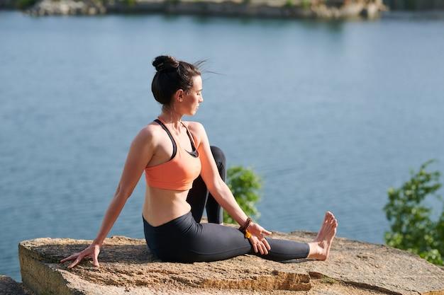 Grave mujer joven con el pelo al viento sentado en la piedra y girando el cuerpo mientras hace marichyasana pose en piedra