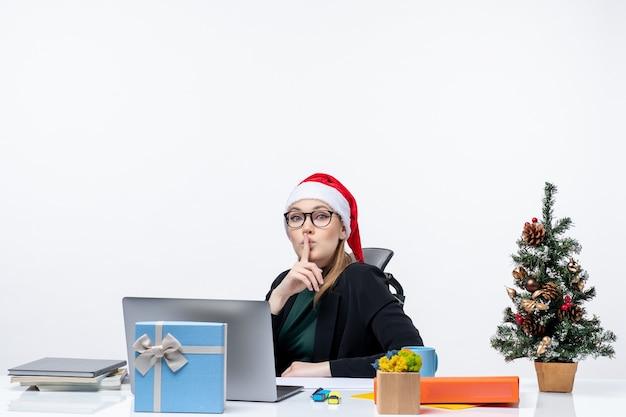 Grave mujer joven con sombrero de santa claus y anteojos sentado en una mesa con un árbol de navidad y un regalo haciendo gesto de silencio sobre fondo blanco.