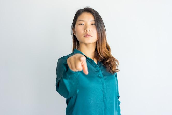 Grave mujer joven y segura de asia apuntando a usted.
