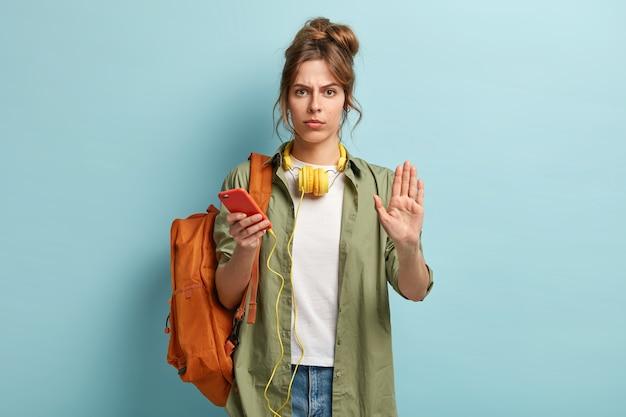 Grave mujer linda pasa tiempo en interiores con un dispositivo moderno, muestra un gesto de parada, pide que disminuya la velocidad, viaja con música y mochila