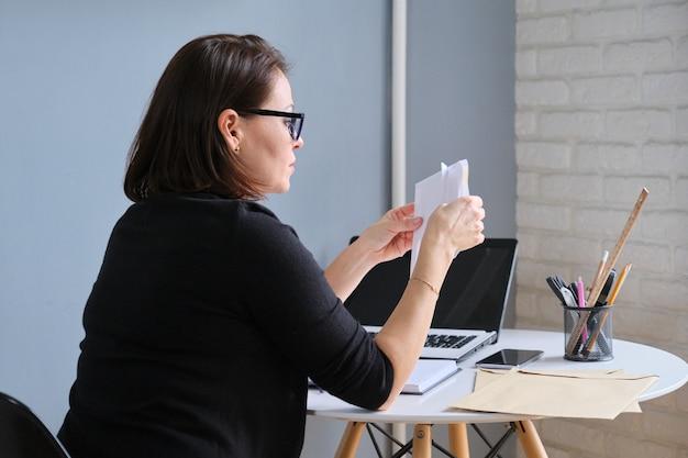 Grave mujer madura sosteniendo documentos comerciales en documentos de manos