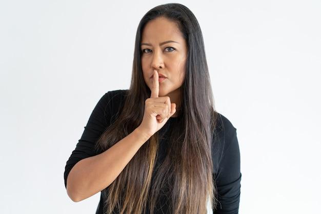 Grave mujer de mediana edad haciendo gesto de silencio