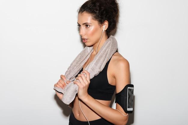 Grave mujer morena rizada fitness con toalla escuchando música