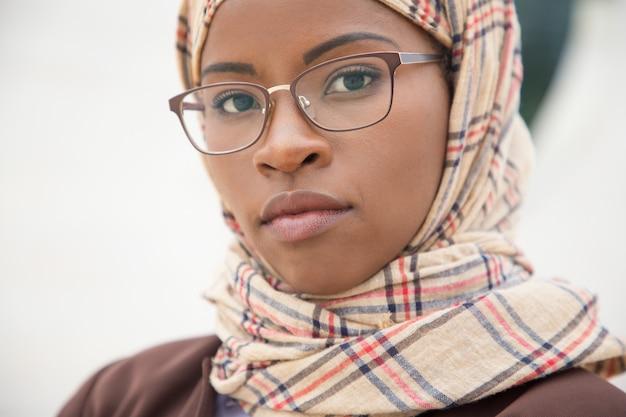 Grave mujer musulmana en gafas posando afuera