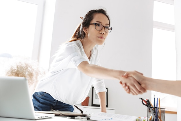 Grave mujer de negocios asiática en anteojos en reunión haciendo apretón de manos en la oficina