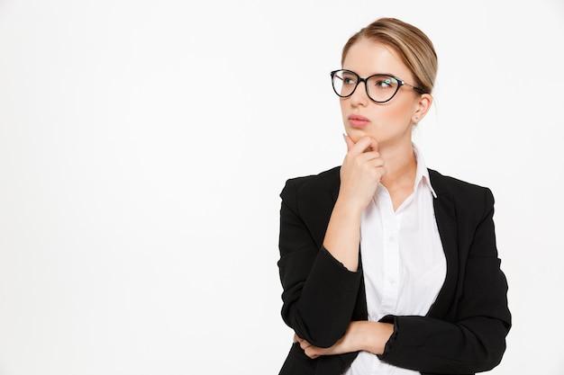 Grave mujer de negocios rubia pensativa en anteojos mirando a otro lado sobre blanco