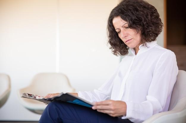 Grave mujer oficinista leyendo revista