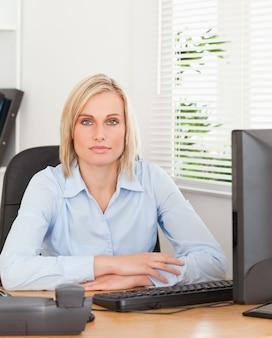 Grave mujer rubia sentada detrás de un escritorio