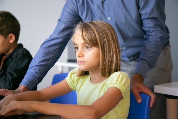 Grave niña caucásica sentada a la mesa en el aula, leyendo texto en la pantalla o viendo una presentación de video