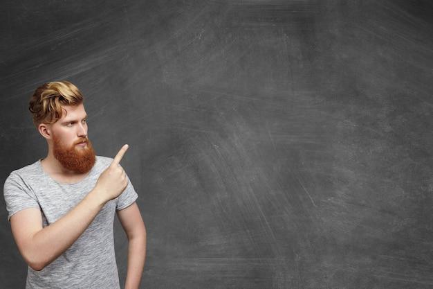 Grave pelirroja barbudo estudiante caucásico hipster vestido con camiseta gris de pie en el aula apuntando a la pared del espacio de copia en blanco con su dedo, mostrando algo en él.