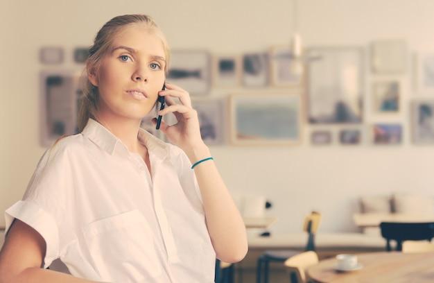 Grave pensativa hermosa joven vestida con camisa blanca, hablando por teléfono móvil, de pie en el espacio de trabajo conjunto