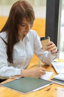 Grave secretaria enfocada trabajando en tableta y tomando café en el lugar de trabajo