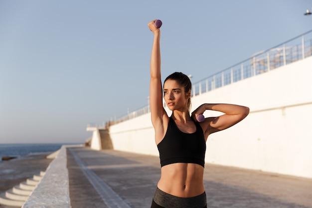 Grave señora concentrada entrenando con pesas en la mañana