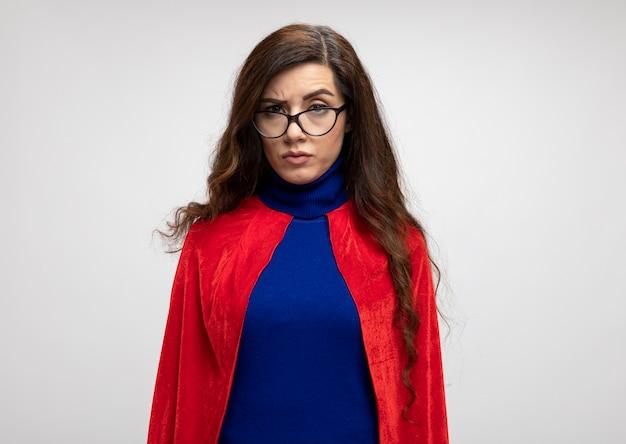 Grave superhéroe caucásico chica con capa roja en gafas ópticas mira a cámara en blanco