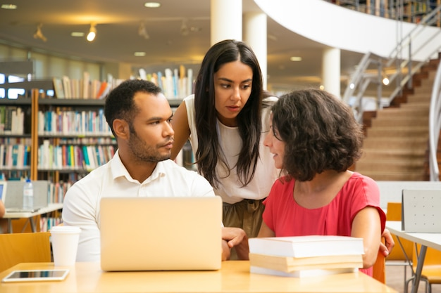 Graves estudiantes sentados a la mesa en la biblioteca con laptop