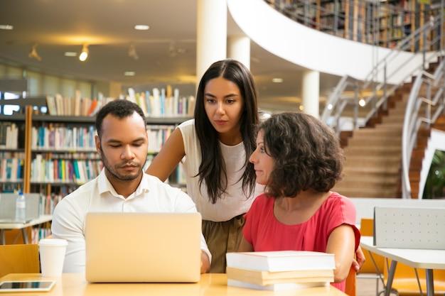 Graves estudiantes sentados a la mesa en la biblioteca trabajando con laptop