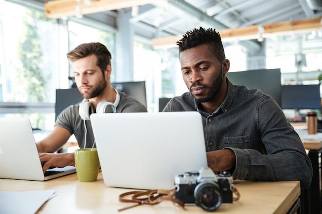 Graves jóvenes colegas sentados en la oficina de coworking