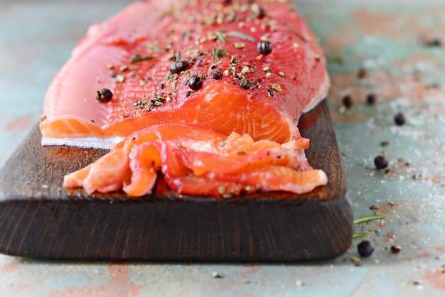Gravlax, salmón especiado curado con remolacha escandinava en el tablero, vista superior, pescado rojo salado