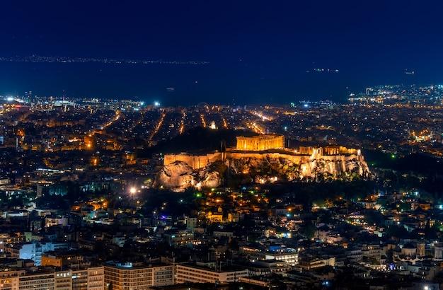 Grecia. atenas. noche de verano. ciudad iluminada y acrópolis. vista aérea