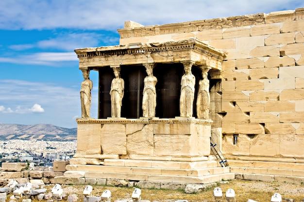 Grecia, atenas, sitio arqueológico de la acrópolis del pórtico erechtheum de las cariátides con la ciudad de atenas