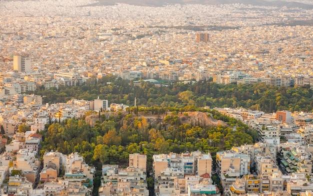 Grecia. cálida tarde de verano sobre los tejados de atenas. edificios residenciales y calles estrechas. parques verdes. vista aérea