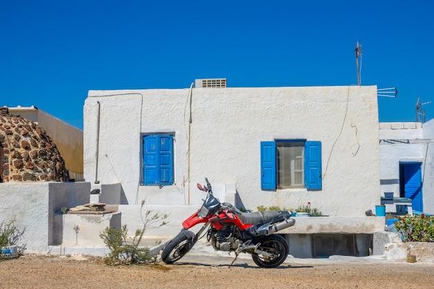 Grecia. ciudad de oia en la isla de santorini. motocicleta roja en frente de una casa de lugareños