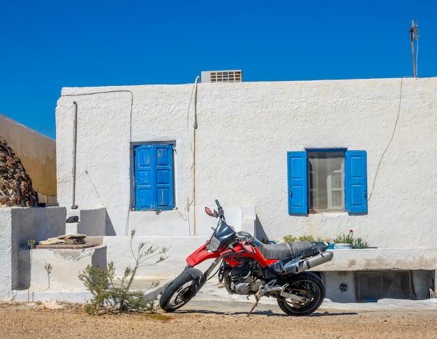 Grecia. ciudad de oia en la isla de santorini. motocicleta roja en frente de la casa.