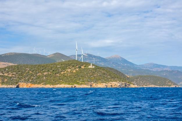 Grecia. costa montañosa del golfo de corinto en un día soleado. antiguo edificio del faro y muchos parques eólicos.