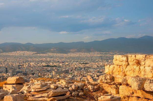 Grecia. puesta de sol en atenas. ruinas de mármol en primer plano. vista desde un punto alto en los tejados de la ciudad.