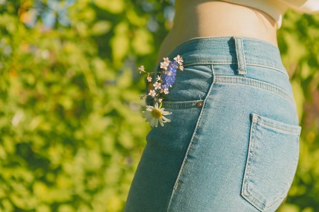 Green park y una chica esbelta en jeans con flores silvestres en el bolsillo.