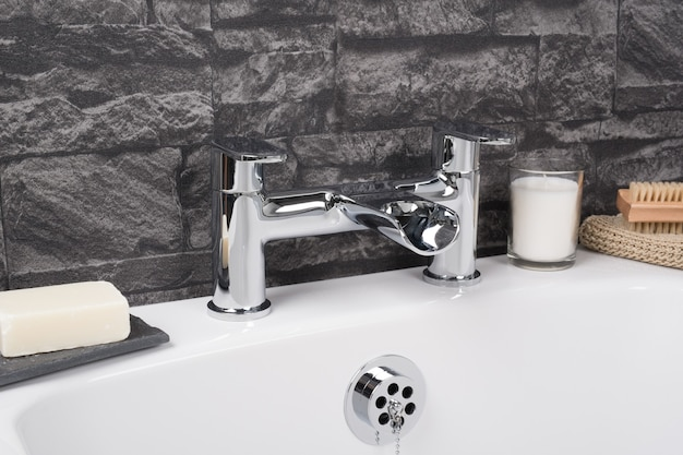 Grifo de acero moderno y nuevo con la bañera de cerámica en el baño.