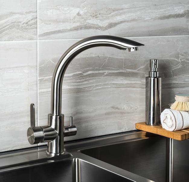 Grifo de acero nuevo y moderno en la cocina.