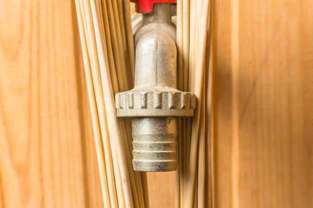 Grifo de agua con escoba de bambú en el baño
