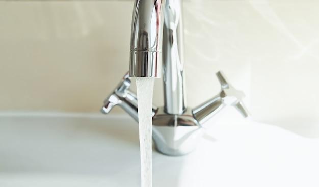 Grifo en el baño con grifo de agua corriente que vierte agua ahorre y proteja el medio ambiente