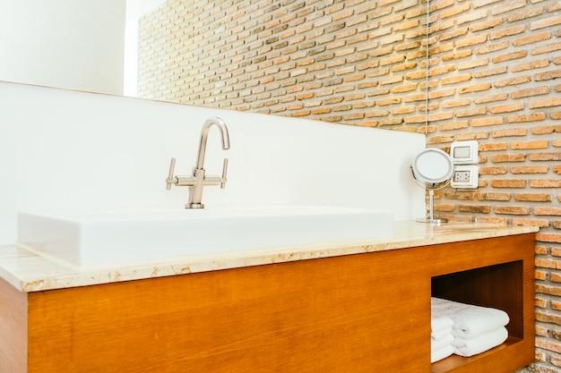 Grifo o grifo de agua y fregadero o lavabo blanco en el baño