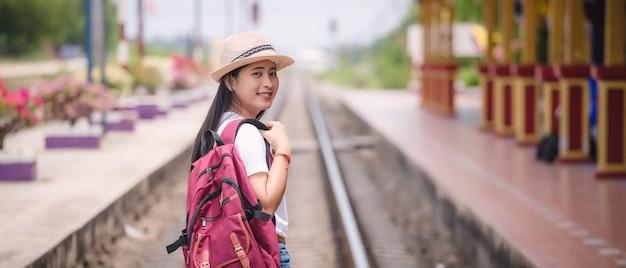 Gril asiático joven que camina en la estación de tren antes de viaje.