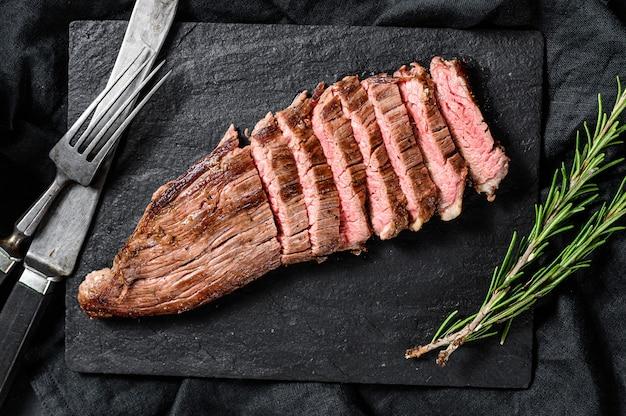 Grill restaurant beef menu - filete de flanco sobre una tabla de piedra negra. fondo negro. vista superior