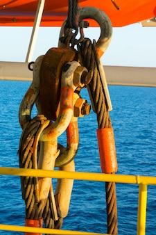 Grillete y honda grandes del metal que cuelgan en la plataforma de perforación petrolífera costera.