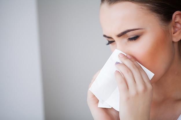 Gripe y mujer enferma. mujer enferma con papel de seda, problema de frío en la cabeza