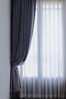 El gris y el blanco ven a través de las cortinas, la decoración interior de la cortina en sala de estar con luz del sol