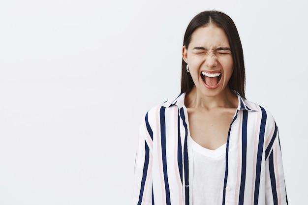 Grita como nadie oye. retrato de mujer emprendedora elegante y atractiva harta en blusa a rayas, cerrando los ojos y gritando, deprimida y aliviada del estrés, gritando en voz alta