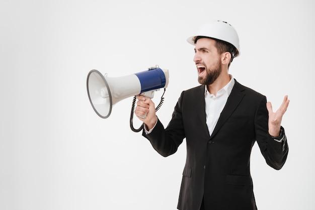 Gritando arquitecto vistiendo casco hablando con altavoz.