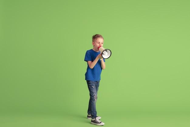 Gritando, llamando. niño feliz jugando y divirtiéndose en la pared verde. niño caucásico en tela brillante se ve juguetón, sonriendo. concepto de educación, infancia, emociones, expresión facial.