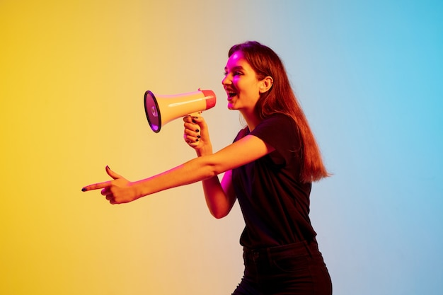 Gritando con megáfono apuntando a joven mujer caucásica en estudio blueyellow degradado