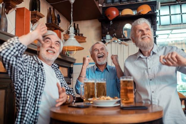 Gritando mientras mira. tres jubilados gritando mientras ve el fútbol en el pub