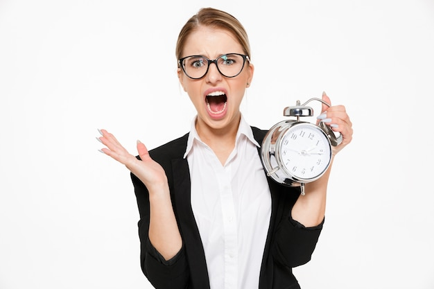 Gritando rubia mujer de negocios en anteojos llega tarde mientras sostiene el despertador y sobre la pared blanca
