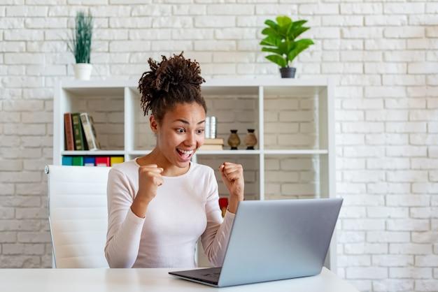 Los gritos felices de una mujer afroamericana hacen un gesto ganador con los puños cerrados