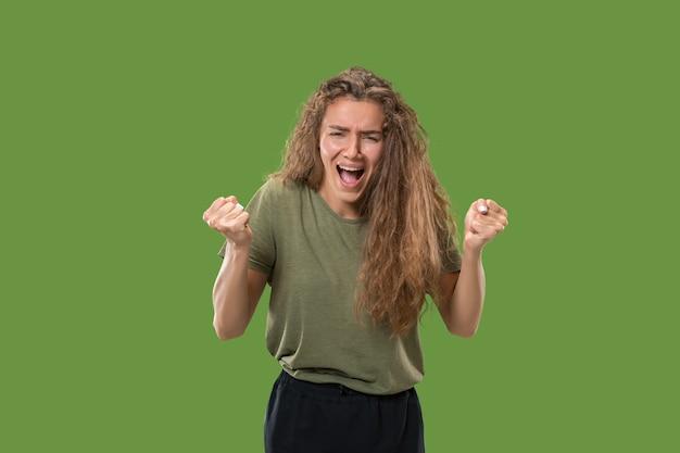 Gritos, odio, rabia. mujer enojada emocional llorando gritando sobre fondo verde de estudio. rostro joven y emocional.
