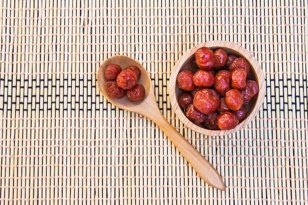 Grosella espinosa en almíbar puesta en un tazón de madera y una cuchara en mimbre de bambú, mayom chueam