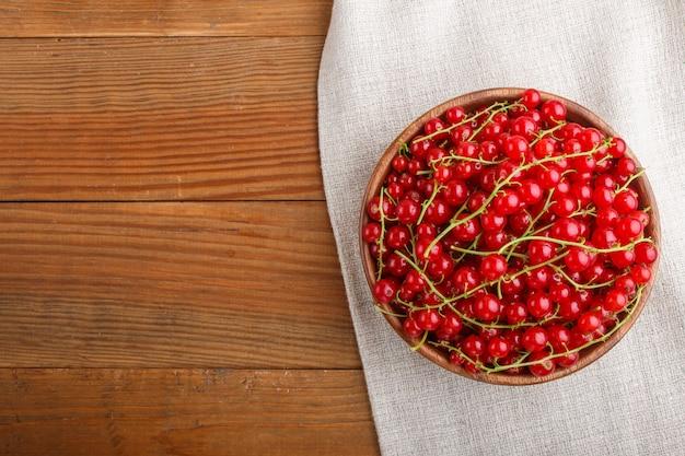 Grosella roja fresca en un tazón de madera sobre fondo de madera